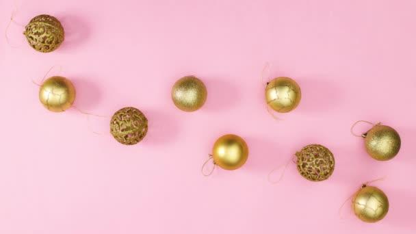 Goldene Weihnachtskugeln und Sterne erscheinen in Pastellrosa. Stop-Motion