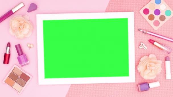Rámeček se zelenou stěnou obklopený pastelovým make-upem a kosmetickými výrobky. Zastavit pohyb