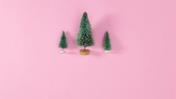 Drei kleine Weihnachtsbäume mit Sternen auf der Spitze erscheinen in pastellrosa. Stop-Motion