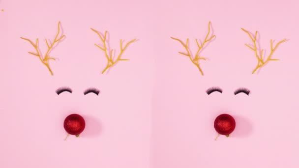 Zwei Rentiere, die mit Augenwimpern auf pastellrosa Hintergrund blinzeln. Stop-Motion
