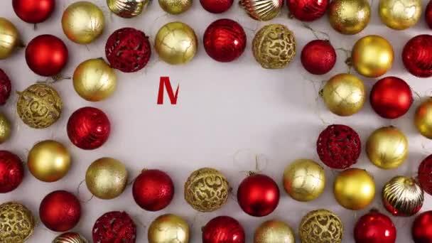 Veselé Vánoce psaní obklopen zlatem a červenými vánoční ozdoby. Zastavit pohyb