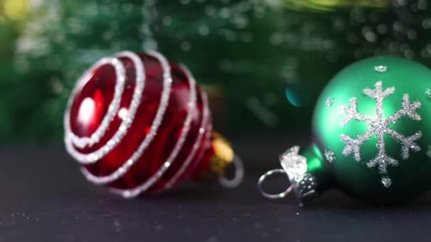 Zblízka tři roztomilé vánoční ozdoby. Zelené, bílé a červené lesklé vánoční ozdoby na stole