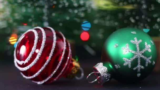 Červené, zelené a bílé lesklé vánoční ozdoby s blikajícími světly vzadu