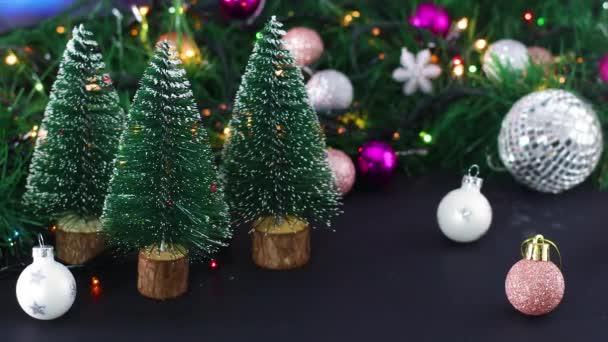 Vánoční lesklá dekorace s blikajícími světly, vánoční ozdoby a malé borovice