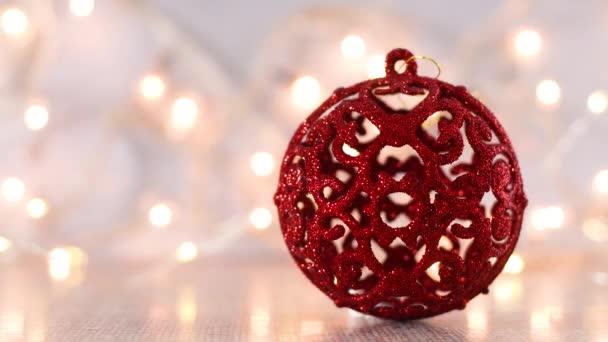 Červený vánoční ovrnament s blikajícími světly vzadu