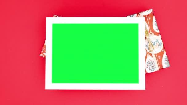 Vánoční dárky a ozdoby se objevují kolem rámu se zelenou obrazovkou. Zastavit pohyb