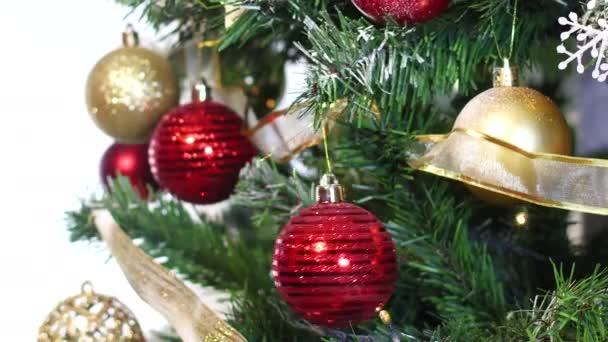 Červená kulatá ozdoba pohybující se na vánočním stromě. Zavřít