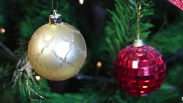 Zlaté a červené vánoční ozdoby na vánočním stromečku s blikajícími světly