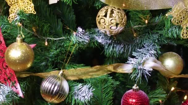 Vánoční stromeček zdobený zlatými a červenými ozdobami a blikajícími světly
