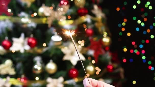 Jiskra hoří před vánočním stromečkem s blikajícími světly