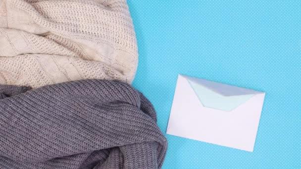Papír v obálce pro psaní přání pro vánoční a zimní dekoraci s ozdobami a blikajícími světly na svetru. Zastavit pohyb