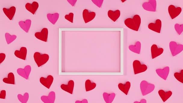 Červená a růžová valentýnská srdíčka se pohybují kolem rámu za textem. Zastavit pohyb
