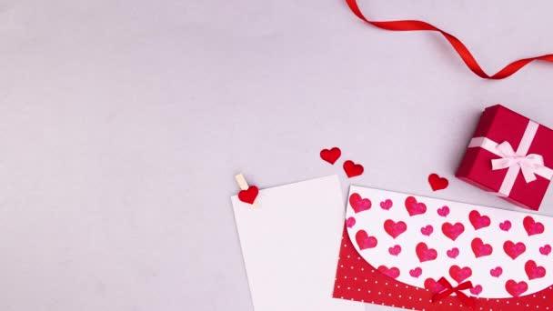 Valentýnský tah s obálkou, dárkem a stuhami na šedé téma. Zastavit pohyb