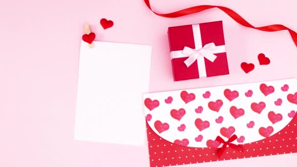 Valentines day envelope and gift move next to paper for text. Stop motion