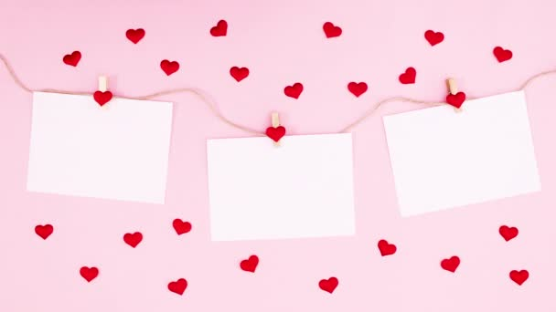 Happy Valentines day text appear on papers hooked on rope surrounded with hearts. Stop motion