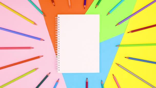 Színes ceruzák pislognak nyitott füzetben. Állj!