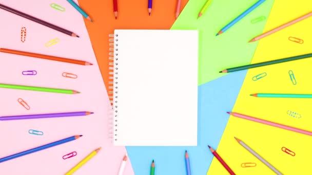Színes ceruzák és gemkapcsok mozognak a füzetben. Állj!