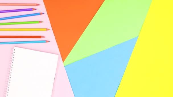 Otevřít zápisník a barevné tužky se objevují na barevném motivu. Zastavit pohyb