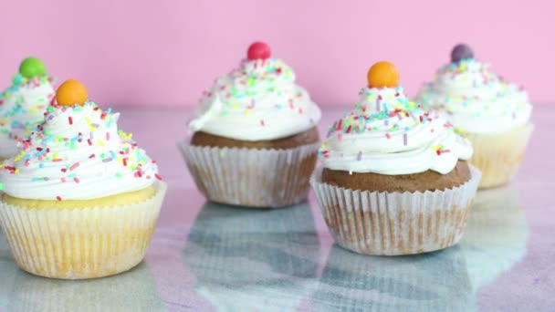 Sweet cup cakes with white cream and crumbs on the table for birthday party