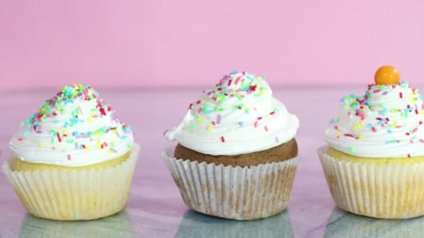 Putting colorful candies on delicious cup cakes with white cream for party