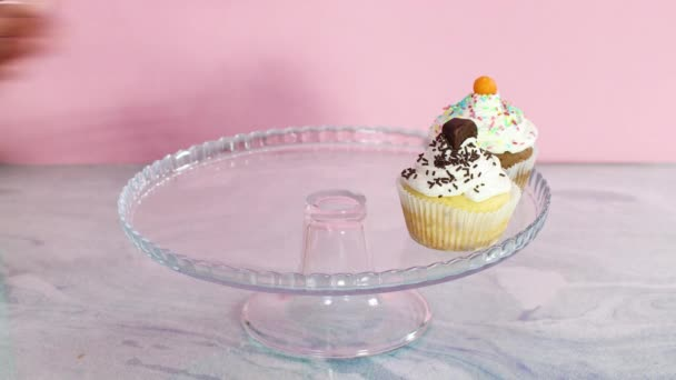 Hand putting cup cakes on crystal plate, decorating for birthday party