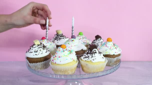putting candles on Cup cakes with cream for birthday party