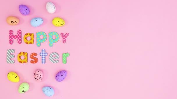 Bunte Eier bewegen sich um den Text Frohe Ostern. Stop-Motion