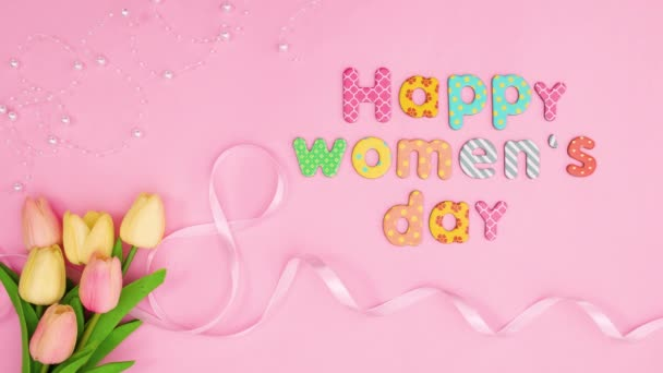 Šťastný den žen text pohybovat na růžové téma s květinami a stuhami. Zastavit pohyb