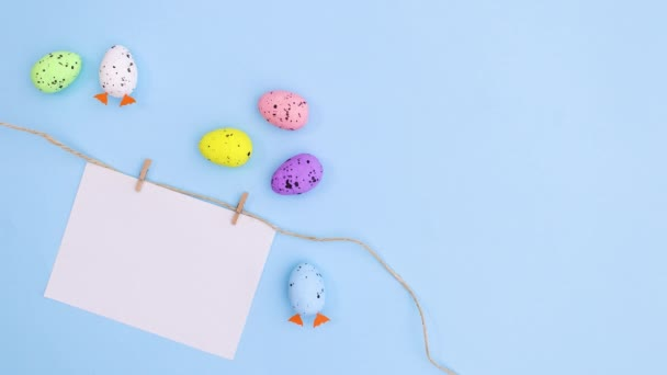 Eggs for Easter move next to paper for text on blue theme. Stop motion