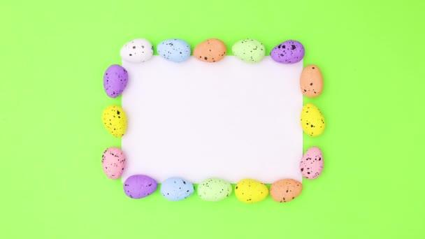 Velikonoční vajíčka se objevují kolem bílého papíru pro text. Zastavit pohyb