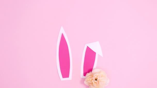 Hasenohren und Blütenarrangements zu Ostern erscheinen auf pastellrosa Hintergrund. Flache Laie-Stop-Bewegung