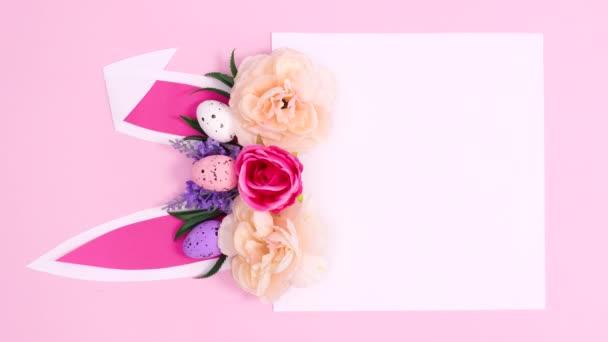 Vertikale kreative Papierkartennotiz mit Hasenohren und Blütenfrühlings-Arrangement auf pastellrosa Hintergrund. Ostern flach legen Stop-Motion-Komposition