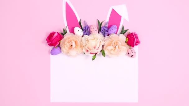 Kreative Osterkomposition mit Papierkartennotiz, Hasenohren und Blütenarrangements auf pastellrosa Hintergrund. Flache Laie-Stop-Bewegung