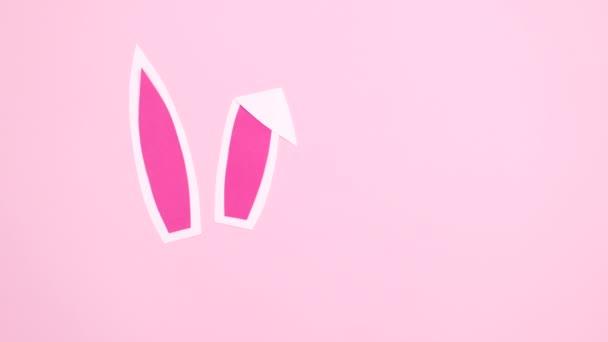 Hasenohren mit Blütenanordnung und Papierkartennotiz erscheinen auf pastellrosa Hintergrund. Osterflache legt Stopp-Bewegung ein