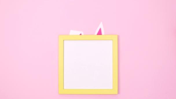 Kreative niedliche Hasenohren und -pfoten erscheinen unter einem Kopierrahmen auf pastellrosa Hintergrund. Minimale flache Lagestopp-Bewegung