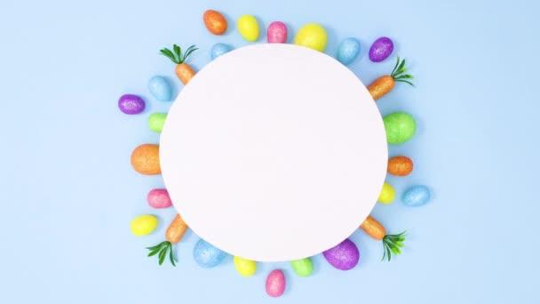 Velikonoční pulzující vajíčka a mrkev se pohybují po papírové kartě na pastelově modrém pozadí. Minimální plochý pohyb zarážky