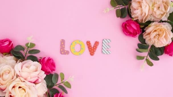 Szerelem szöveg mozog virágos elrendezése pasztell fényes rózsaszín háttér. Stop motion sík fektetés