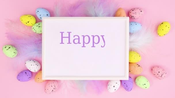 Frohe Ostern schreiben in Rahmen mit Eiern und Federn auf pastellrosa Hintergrund umgeben. Stop-Motion