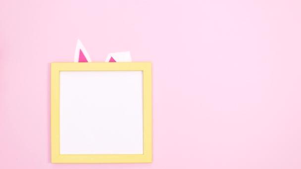 Frohe Ostern schreiben im Rahmen mit Hasenohren und Pfoten auf pastellrosa Hintergrund. Stop-Motion