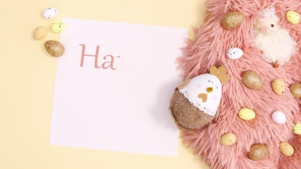 Frohe Ostern schreiben auf Papier mit Osterarrangements auf pastellgelbem Hintergrund, Stop motion