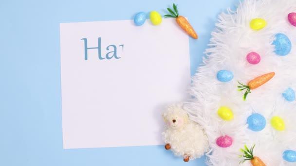 Frohe Ostern Text schreiben auf Papier mit lebendiger Dekoration auf pastellblauem Hintergrund. Stop-Motion