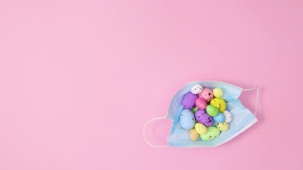 Gesichtsmaske mit Ostereiern erscheint auf pastellrosa Hintergrund. Stoppbewegungen flach legen