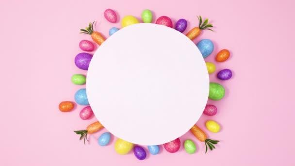 Eier bewegen unter Papierkartennotiz auf pastellrosa Hintergrund. Stoppbewegungen flach legen