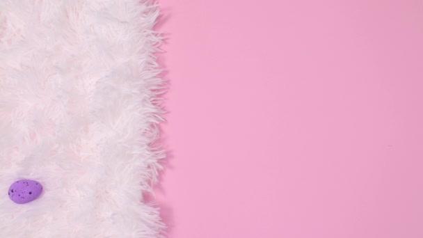 Ostereier erscheinen auf weißem Fell und Pappkarton auf pastellrosa Hintergrund. Stop-Motion