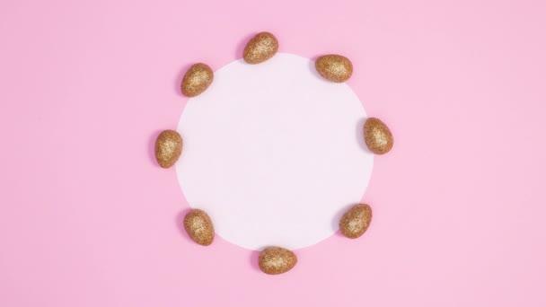Trendige goldene Ostereier erscheinen rund um Papierkartennotiz auf pastellrosa Hintergrund. Stop-Motion