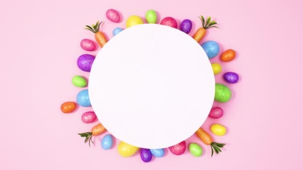 Lebendige Ostereier erscheinen unter runden Papierkartennotizen auf pastellrosa Hintergrund. Stoppbewegungen flach legen