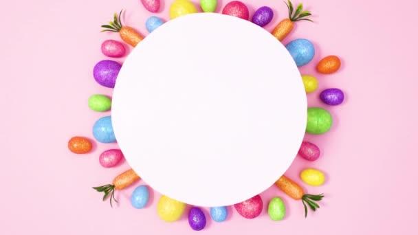 Papierkartennotiz umgeben von lebendigen Ostereiern auf pastellrosa Hintergrund. Stop-Motion