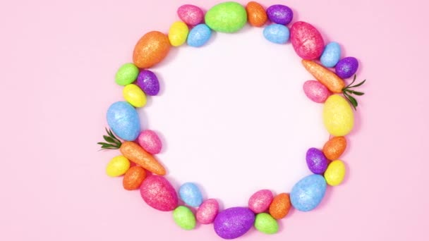 Papírová karta obklopená pulzujícími velikonočními vejci na pastelově růžovém pozadí. Zastavit pohyb