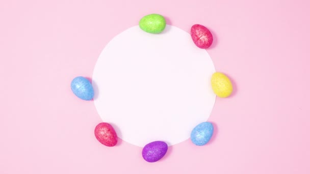 Lebendige Ostereier erscheinen um Papierkartennotizen auf pastellrosa Hintergrund. Stop-Motion