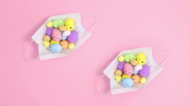 Zwei kreative Gesichtsmasken mit Ostereiern auf pastellrosa Hintergrund. Stop-Motion